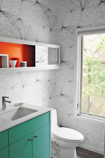 When upgrading this 1960s midcentury home in Austin, Texas, local architects local architects Rick and Cindy Black created a new powder room with punchy Jill Malek wallpaper, a turquoise built-in cabinet and vanity support and a mirrored shelving unit with a back wall painted orange-red.
