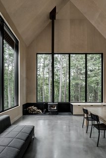This voluminous cabin in Austin, Quebec, has a sharply pitched roof and a bright and lofty interior that strikes surprising contrast to its austere, angular exterior.