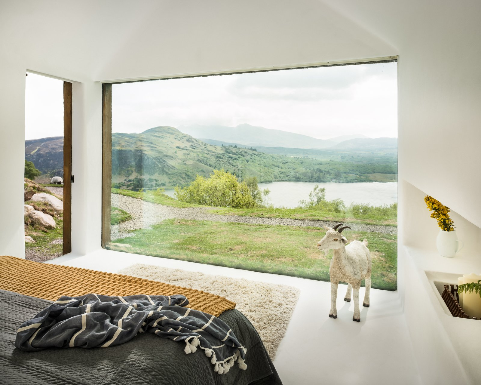 Windows and Picture Window Type The Lost Cottage vacation rental is nestled in the remote lakeside town of Treangarriv in County Kerry, Ireland. The principal bedroom features a massive picture window that looks out over Caragh Lake and the surrounding farmland. A glass roof was also installed above the sunken tub in the bathroom so that guests can gaze up at the stars in the International Dark Sky Reserve.  Dwell's Favorite Photos from 7 Vacation Rentals in Ireland That Put a Spin on the Classic Cottage