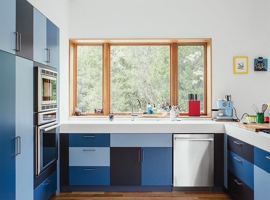 Kitchen, Microwave, Wall Oven, Range, Colorful Cabinet, Medium Hardwood Floor, and Dishwasher In this home near Knoxville Tennessee, the owner's friend Forrest Kirkpatrick constructed laminate Mondrian-like kitchen cabinets in three alternating shades of blue.  Photos from 12 Electrifying Kitchens That Are Unapologetic About Color