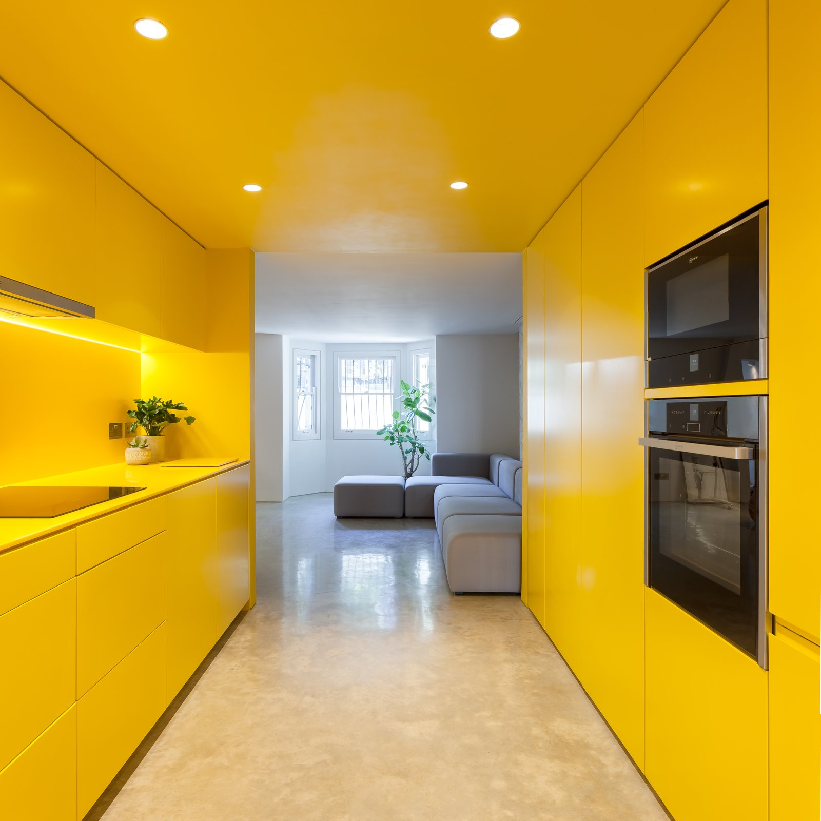 Kitchen, Accent Lighting, Cooktops, Recessed Lighting, Colorful Cabinet, and Wall Oven Designed by London-based practice RUSSIAN FOR FISH, this remodeled Victorian home has an almost completely yellow kitchen. Being in this space feels like being immersed in bright sunlight.  Photos from 12 Electrifying Kitchens That Are Unapologetic About Color