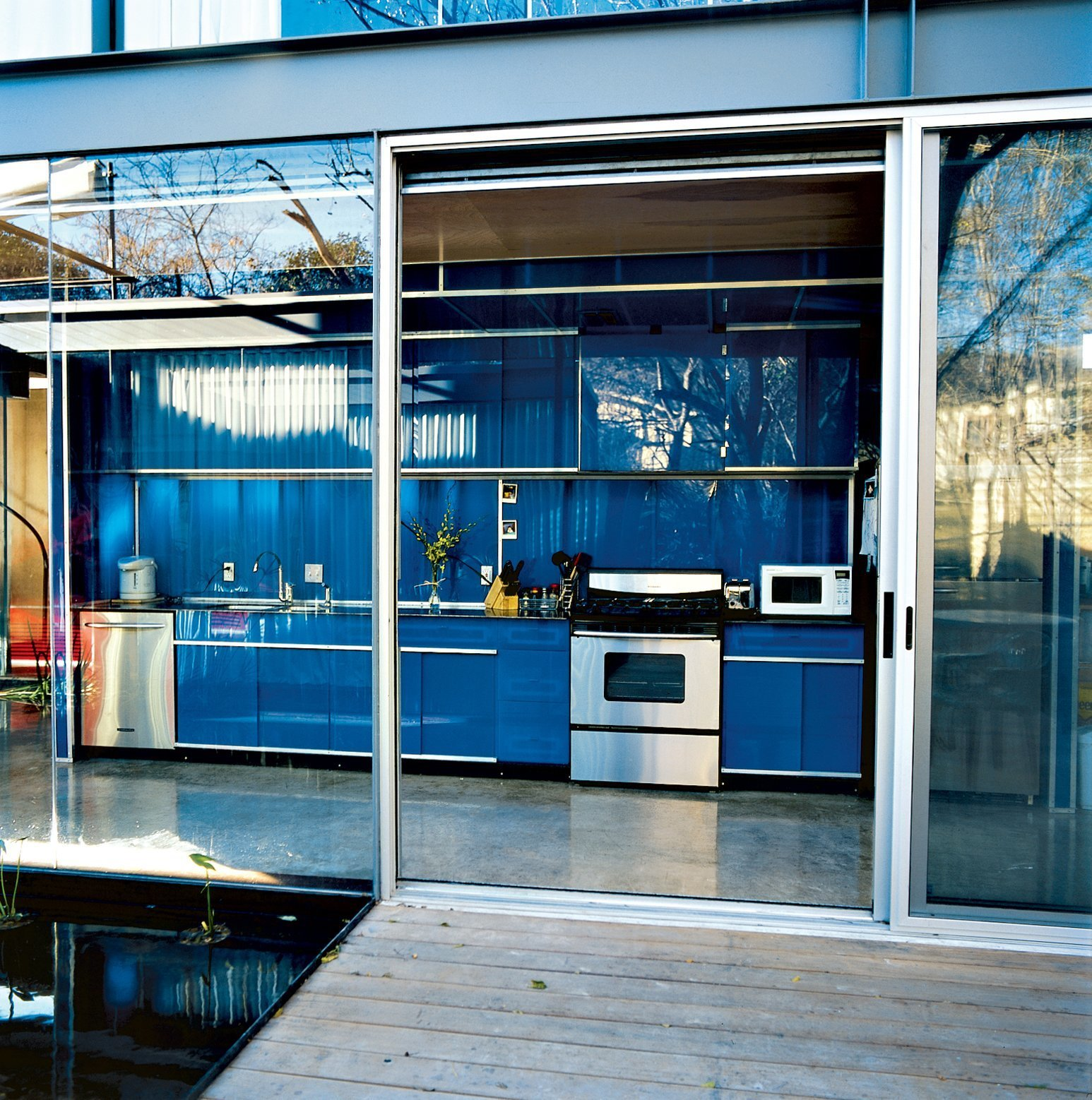 Kitchen, Range, Colorful, Microwave, Dishwasher, Wall Oven, and Concrete The inaugural project of Bercy Chen Studio, this home in Austin, Texas has a cobalt blue galley-style kitchen that is free from visible knobs and hinges.  Best Kitchen Concrete Colorful Photos