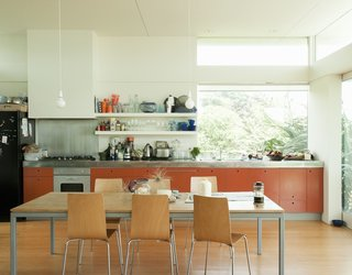 New Zealand architect Gerald Parsonson and his wife, Kate, designed their vacation beach home in Paraparaumu with an open-plan kitchen with open shelves, bar light bulbs, and bright orange MDF cabinets.