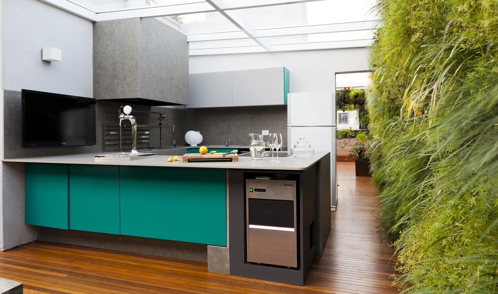 Kitchen, Colorful Cabinet, Medium Hardwood Floor, Wall Lighting, Undermount Sink, Refrigerator, and Beverage Center This São Paulo by Casa14 Arquitetura has plenty or large thresholds and open spaces, and a kitchen with turquoise cabinets surrounded by lush vertical green walls.  Photo 11 of 13 in 12 Electrifying Kitchens That Are Unapologetic About Color