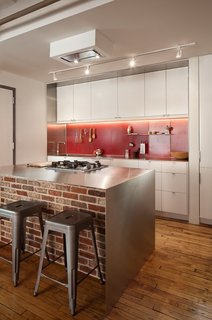 Bunker Workshop used bright, red steel pegboard for the backsplash in this kitchen in Boston loft apartment in a former textile factory.