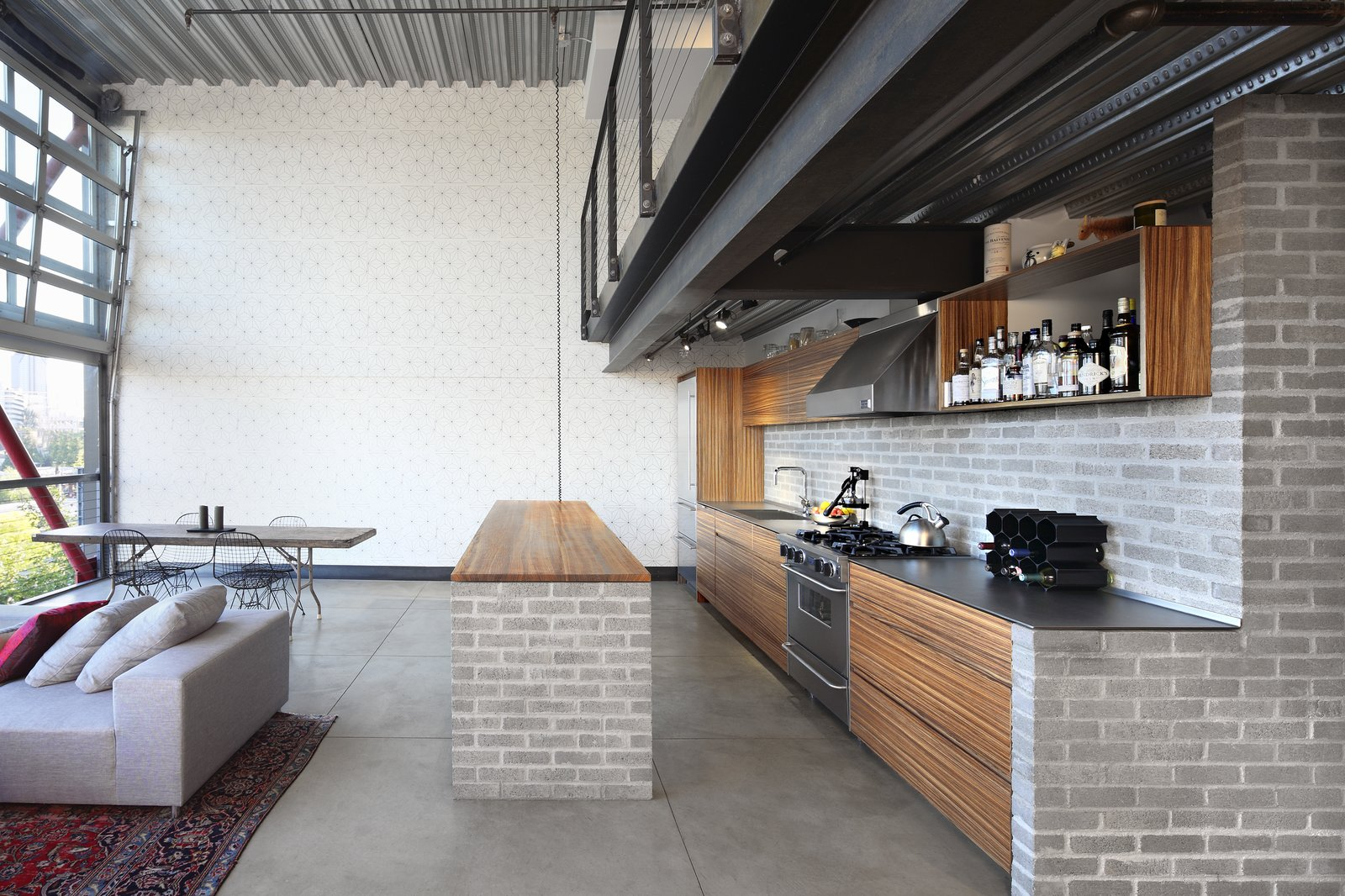 Kitchen, Wood Cabinet, Range Hood, Concrete Floor, Wall Oven, Track Lighting, Drop In Sink, Brick Backsplashe, Rug Floor, Wood Counter, Refrigerator, Range, Open Cabinet, and Beverage Center Here, an industrial material palette—with a concrete brick backsplash and counter foundation, and zinc-plated pan-decking ceilings—complement the development's edgy facade.  Photos from Before & After: Two Game-Changing Kitchen Renovations by a Seattle Studio
