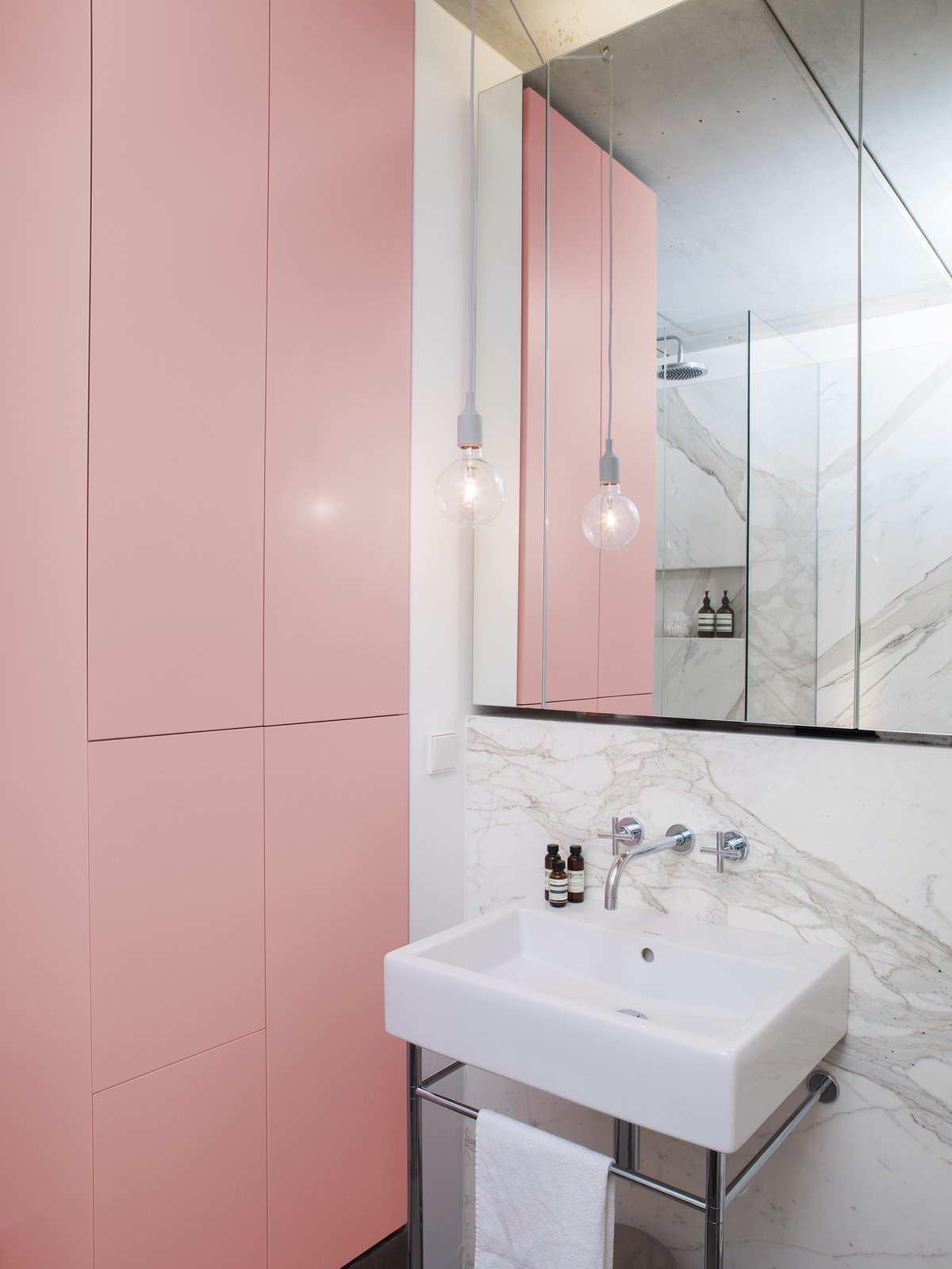 Bath Room, Pendant Lighting, Marble Wall, and Wall Mount Sink Smooth, handleless joinery are a classical, but nonetheless creative way to make storage systems beautifully discreet with ample room for storage.  Photos from 8 Bathroom Storage Hacks You Probably Haven't Tried Yet
