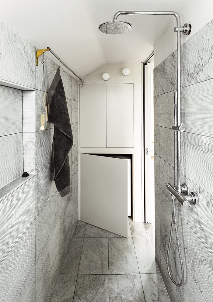Bath Room, Marble Floor, Wall Lighting, Marble Wall, and Full Shower When architects Silvia Ullmayer and Allan Sylvester worked with joiner Roger Hynam to reinvent an apartment for metalworker Simone ten Hompel, they created a covered space in the bathroom to conceal the front loader washing machine.  Photo 5 of 8 in 8 Bathroom Storage Hacks You Probably Haven't Tried Yet