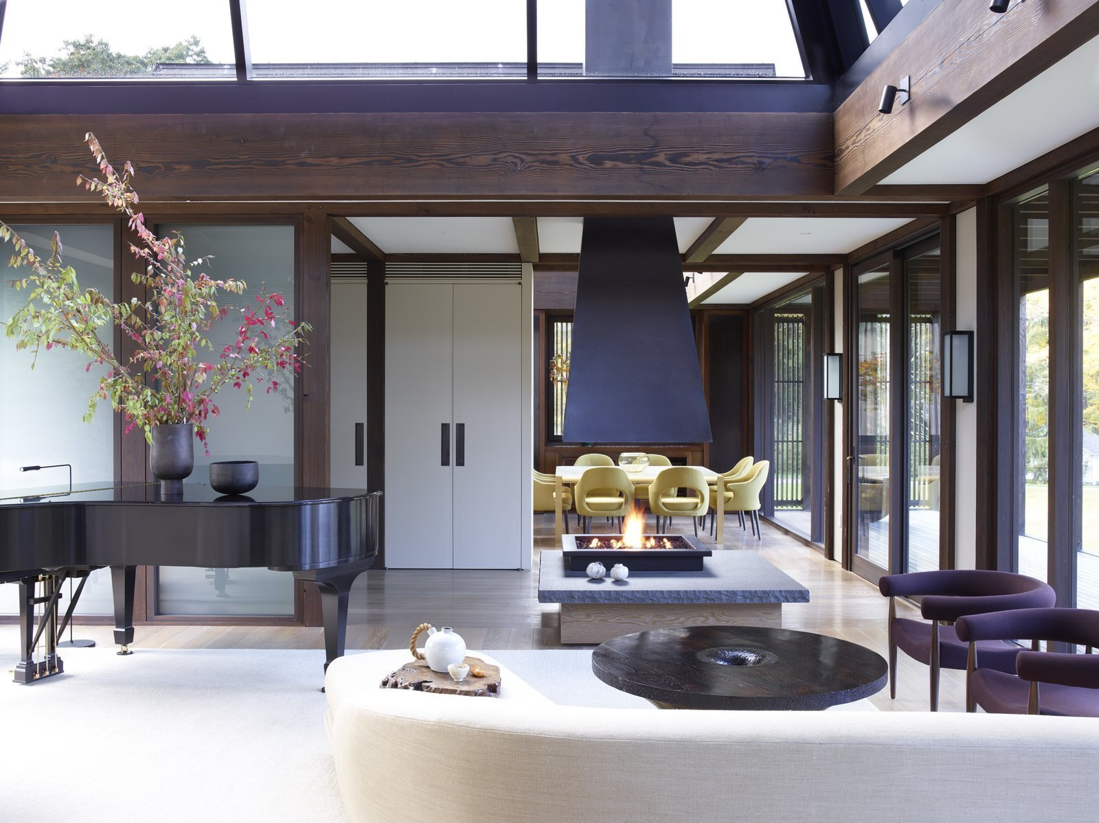 Living, Light Hardwood, Coffee Tables, Chair, Standard Layout, Wall, Rug, Storage, Gas Burning, and Two-Sided Fashion designer Josie and her husband Ken Natori are big fans of traditional Japanese architecture, so when Brooklyn-based practice Tsao & McKown Architects designed their home in Pound Ridge, New York, they used a heavy, exposed-timber structure, and included Japanese-style gardens and landscaping.  Living Two-Sided Standard Layout Photos from 10 Zen Homes That Champion Japanese Design