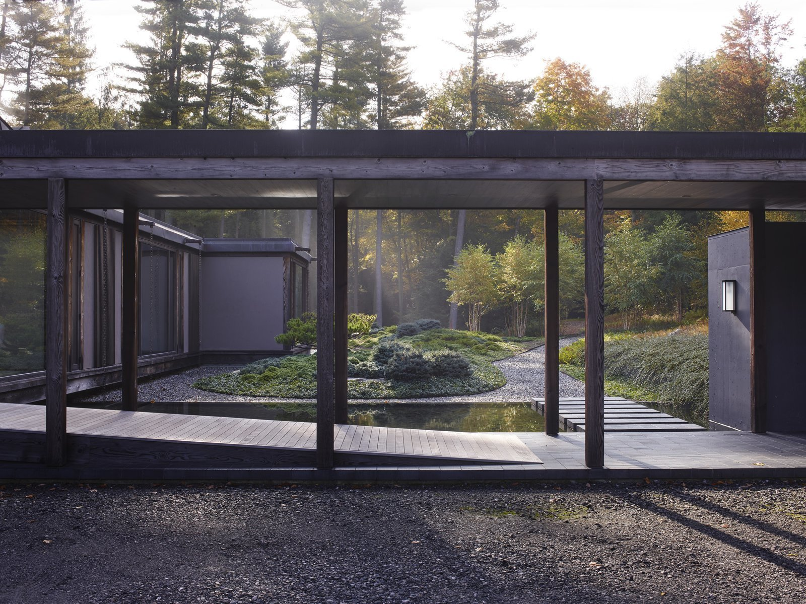 Outdoor, Garden, Hardscapes, Grass, Walkways, Trees, Gardens, Shrubs, and Wood Patio, Porch, Deck Fashion designer Josie and her husband Ken Natori are big fans of traditional Japanese architecture, so when Brooklyn-based practice Tsao & McKown Architects designed their home in Pound Ridge, New York, they used a heavy, exposed-timber structure, and included Japanese-style gardens and landscaping.  Best Photos from 10 Zen Homes That Champion Japanese Design