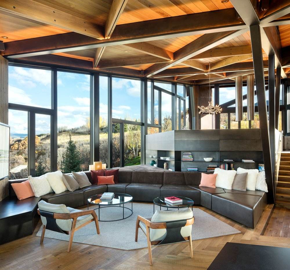 Living Room, Pendant Lighting, Coffee Tables, Chair, Recessed Lighting, Bookcase, Medium Hardwood Floor, Sectional, and Rug Floor Friday 1 chairs by Avenue Road face far-reaching views.  Photo 11 of 16 in An Angular Mountain Retreat in Colorado Captures Breathtaking Views