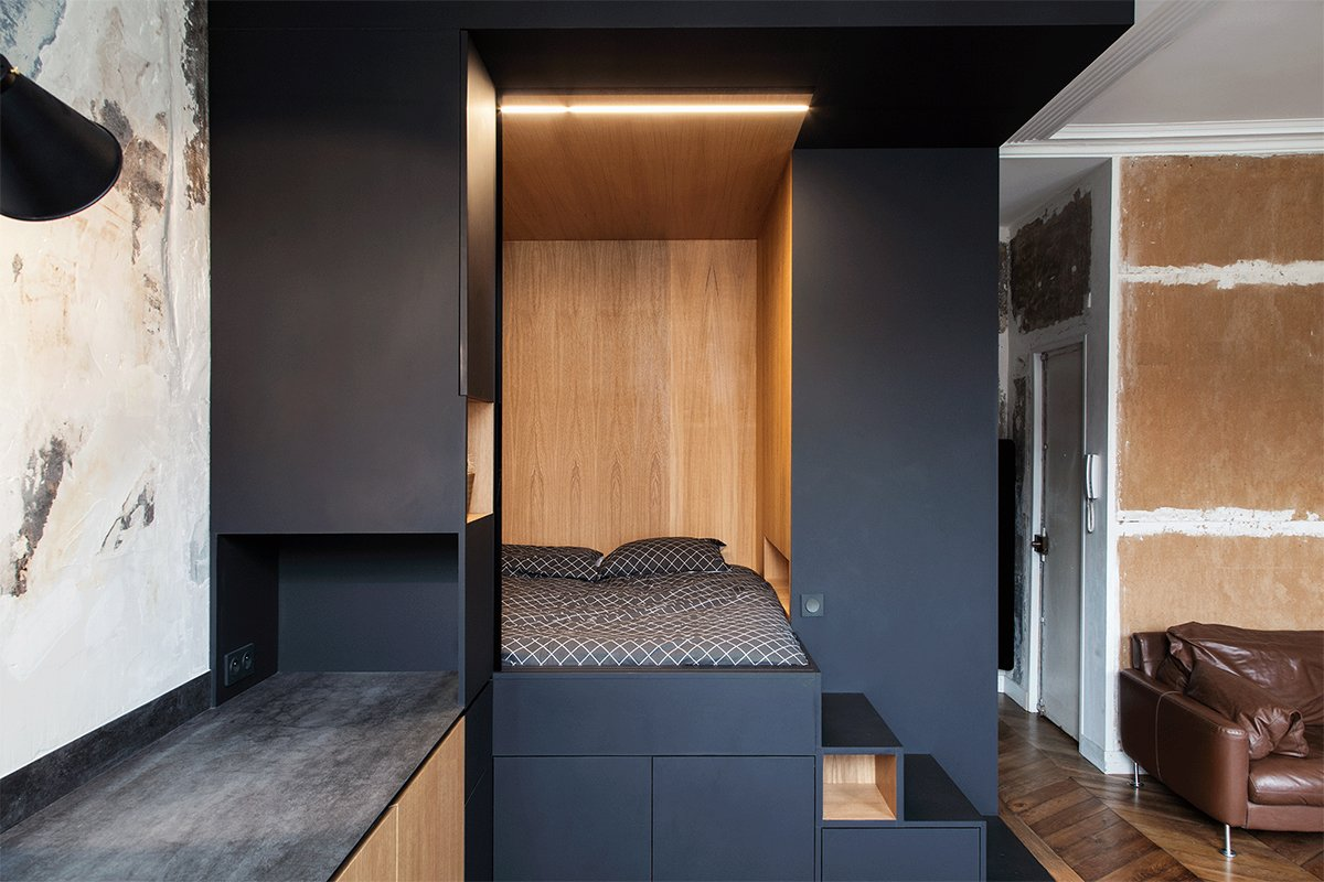"Bedroom, Accent Lighting, Medium Hardwood Floor, Bed, Shelves, Storage, and Wall Lighting A ""space cube"", made of Fenix NTM's matte nanotech material combined with warm oak serves as sleeping nook and storage.  Best Photos from A Multipurpose Bedroom Box Is This Tiny Apartment's Genius Solution"