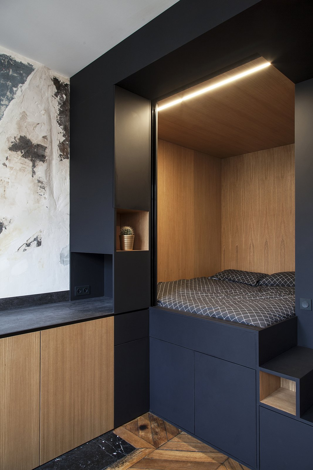 Bedroom, Bed, Shelves, Accent Lighting, Medium Hardwood Floor, and Storage The cube is connected to a discrete kitchenette with built-in cabinetry.  Photo 5 of 9 in A Multipurpose Bedroom Box Is This Tiny Apartment's Genius Solution