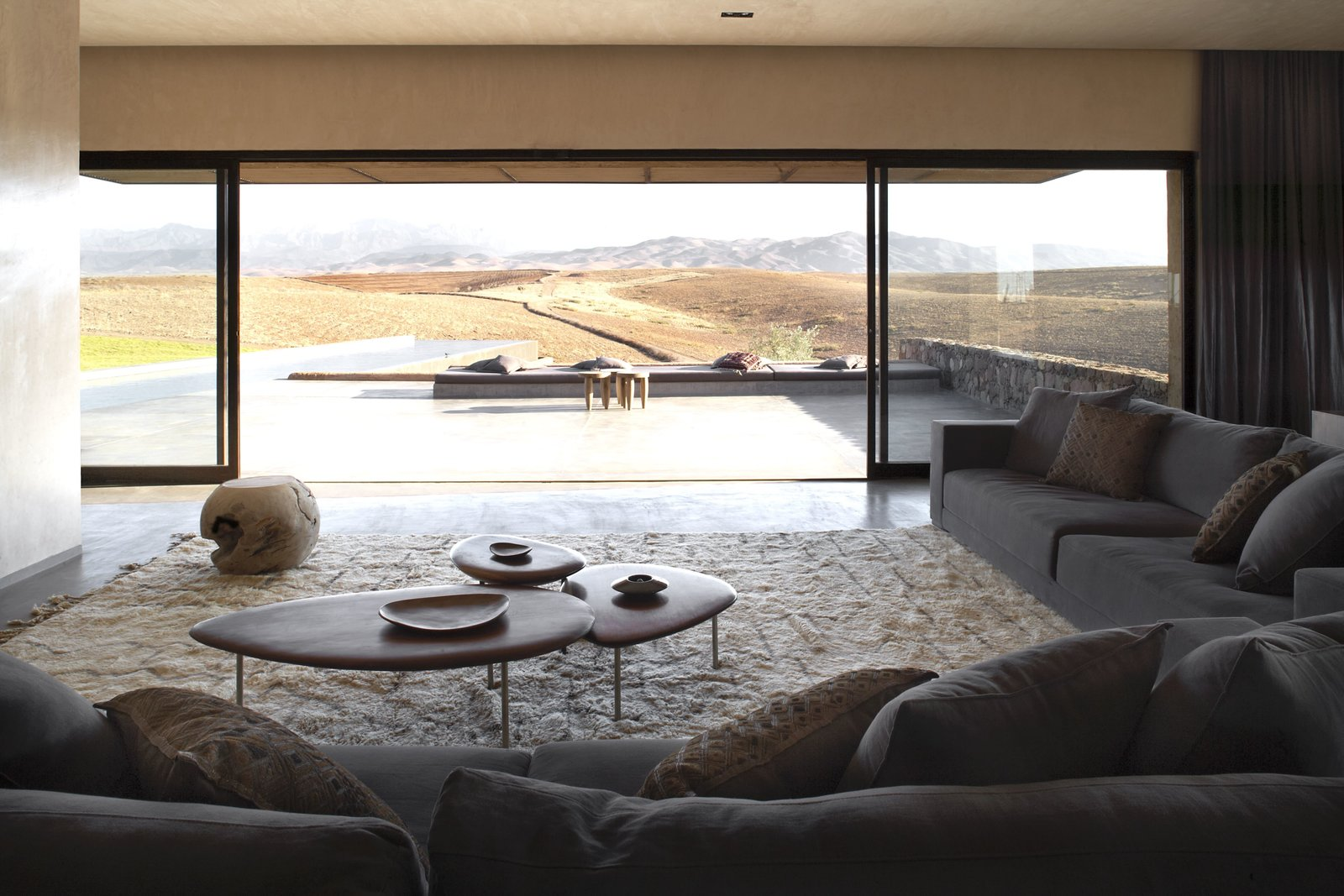 Living Room, Stools, Coffee Tables, Concrete Floor, Sectional, End Tables, Recessed Lighting, and Rug Floor Villa K look to views of the Atlas Mountains.  Photo 1 of 10 in 4 Enchanting Moroccan Villas by French Duo Studio KO