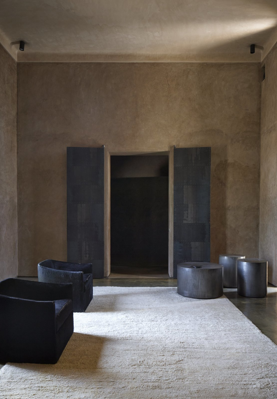 Living Room, Ceiling Lighting, Chair, Concrete Floor, End Tables, and Rug Floor Interiors of Villa D.  Photo 3 of 10 in 4 Enchanting Moroccan Villas by French Duo Studio KO