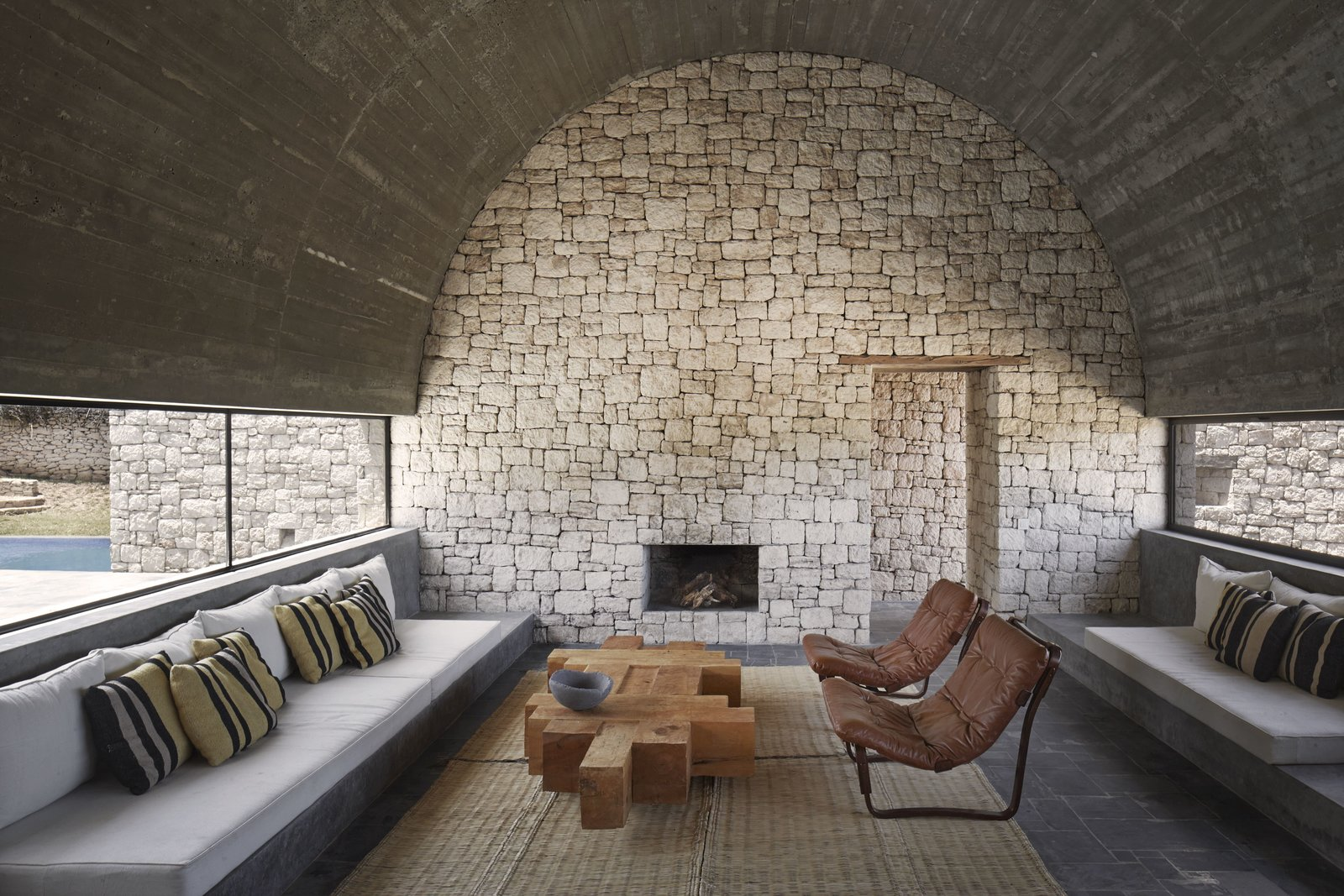 Living Room, Bench, Coffee Tables, Chair, Wood Burning Fireplace, Rug Floor, and Slate Floor Materials such as unpolished stone, used for the interior walls speak louder than statement furniture or décor.  Photo 5 of 10 in 4 Enchanting Moroccan Villas by French Duo Studio KO