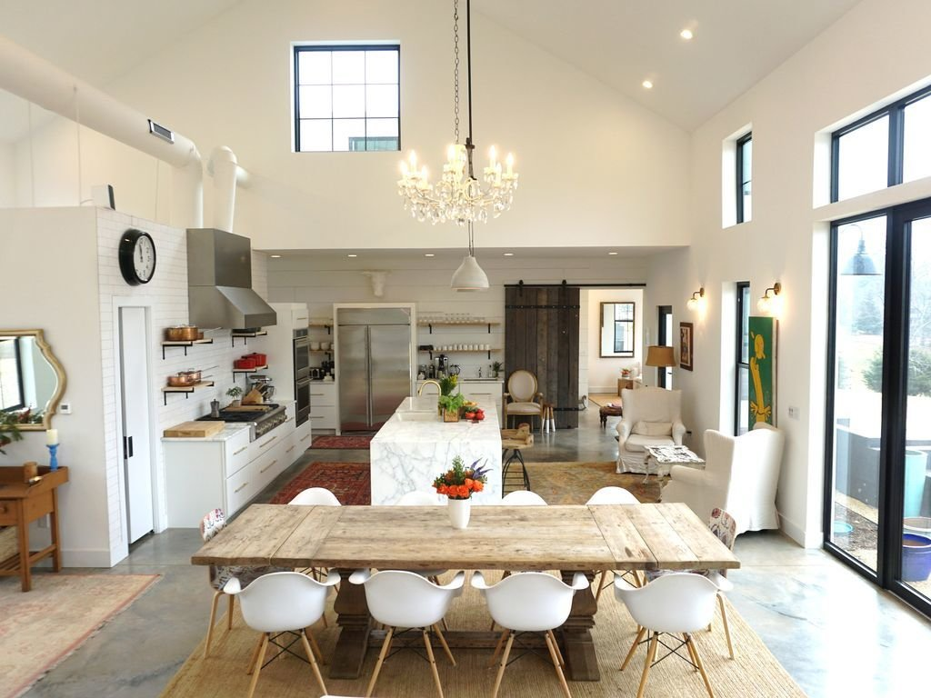 Dining Room, Pendant Lighting, Chair, Concrete Floor, Table, Ceiling Lighting, Rug Floor, Stools, and Bar A farmhouse with 28-feet-high ceilings in Charlottesville, Virginia  Photo 4 of 8 in 7 Modern Farmhouses to Rent For the Most Picturesque Vacation Ever from Modern Farmhouses