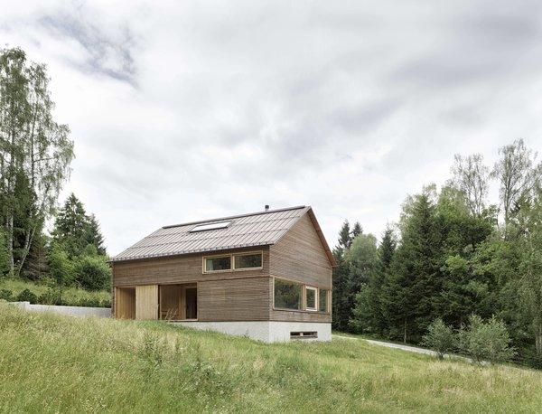 Innauer Matt Architekten designed the house as simple wooden building resting atop a solid, reinforced concrete plinth.