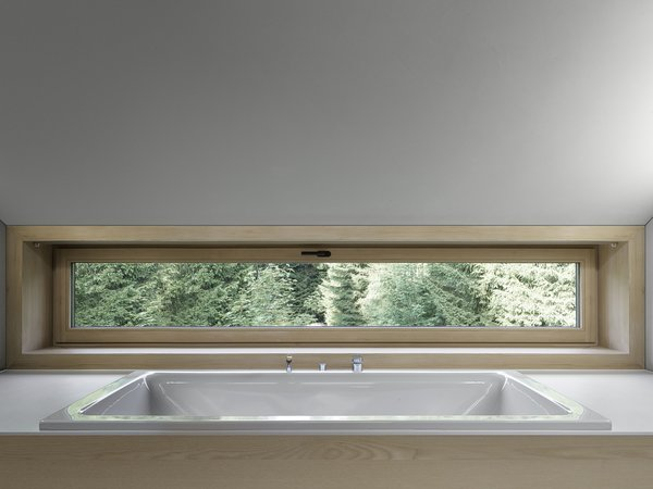 A bathtub that looks out to views of the trees,
