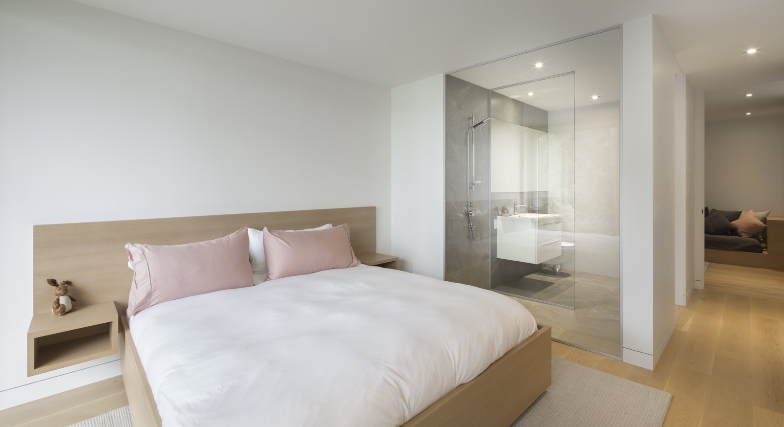 Bedroom, Bed, Night Stands, Light Hardwood Floor, Recessed Lighting, and Shelves A fuss-free, elegant and modern bedroom.  Photo 7 of 14 in A Lakeside Retreat in Quebec Looks Sharp With a Blade-Like Roof