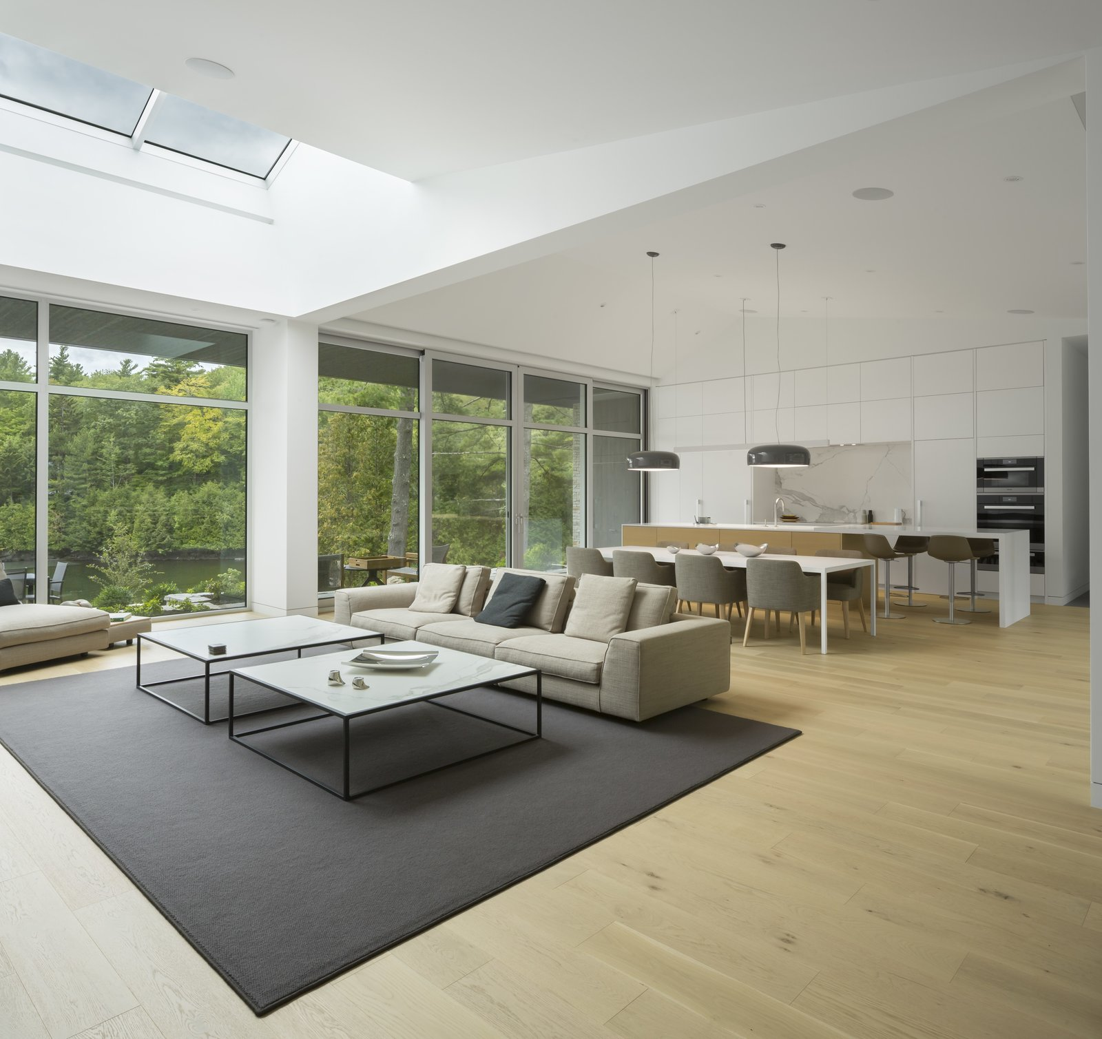 Living Room, Sofa, Coffee Tables, and Light Hardwood Floor A skylight brings plenty of natural light into the living room.  Photo 6 of 14 in A Lakeside Retreat in Quebec Looks Sharp With a Blade-Like Roof