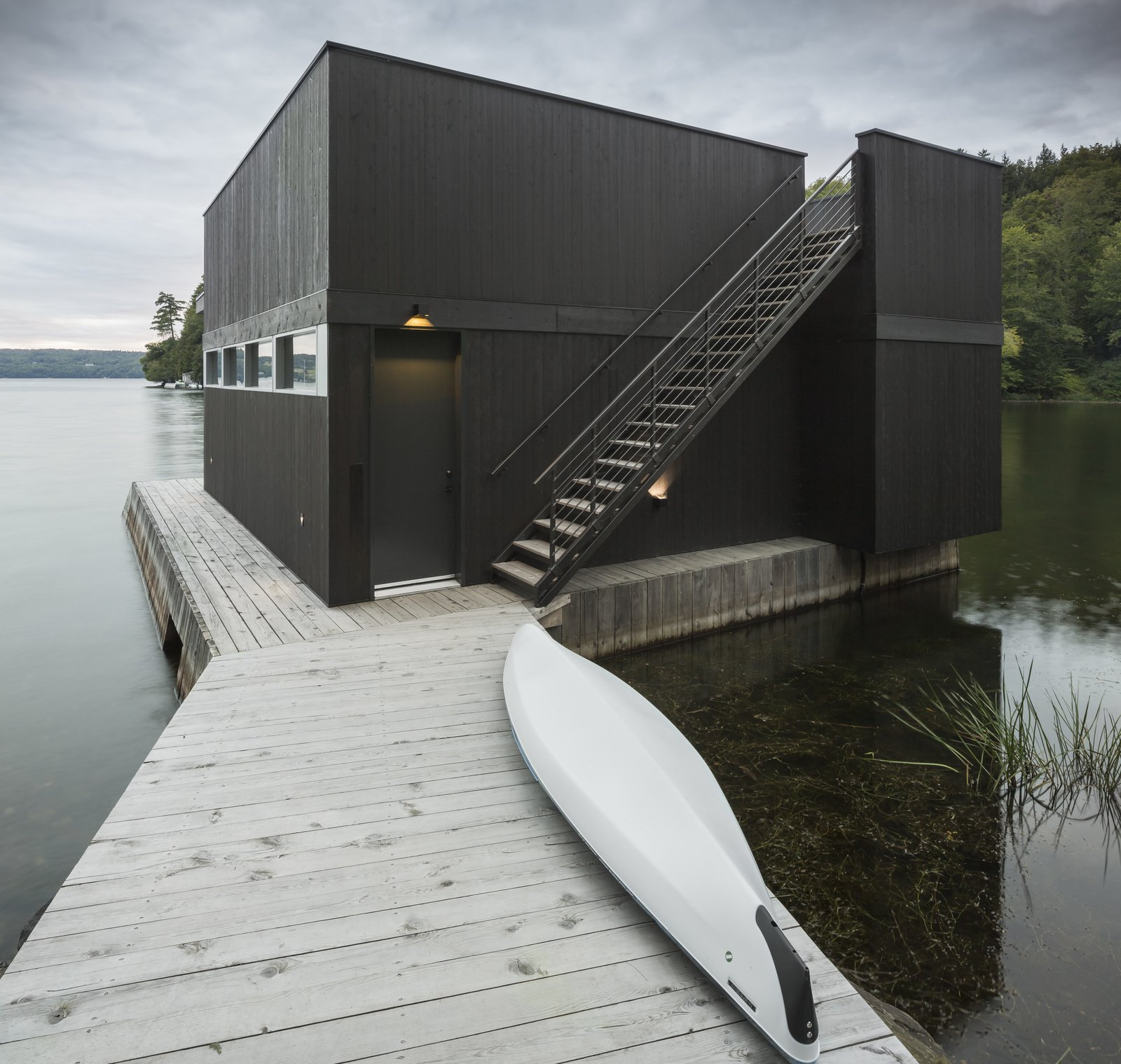 Exterior, Boathouse Building Type, and Flat RoofLine On the edge of the lake is a boathouse with a kitchenette and roof terrace.  Photo 12 of 14 in A Lakeside Retreat in Quebec Looks Sharp With a Blade-Like Roof