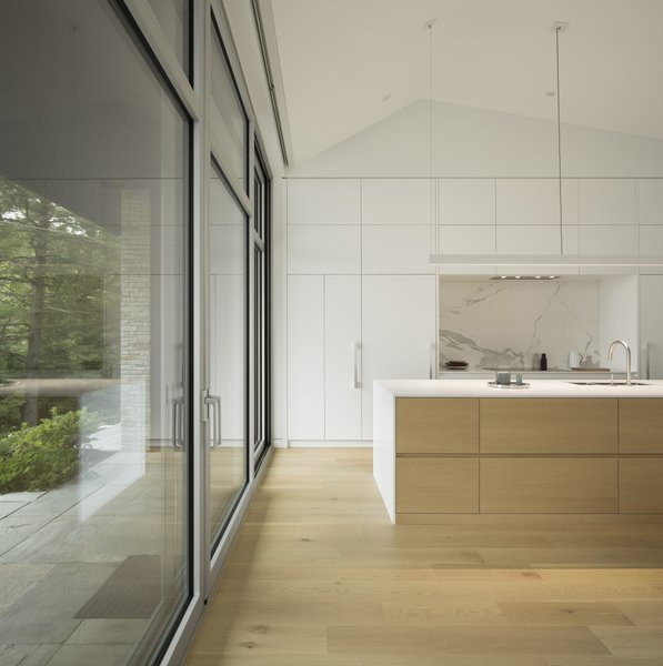 This lakeside home in Quebec boasts a white kitchen with an elegant, white marble backsplash that adds just a touch of pizzazz to an otherwise simple and minimalist open kitchen.