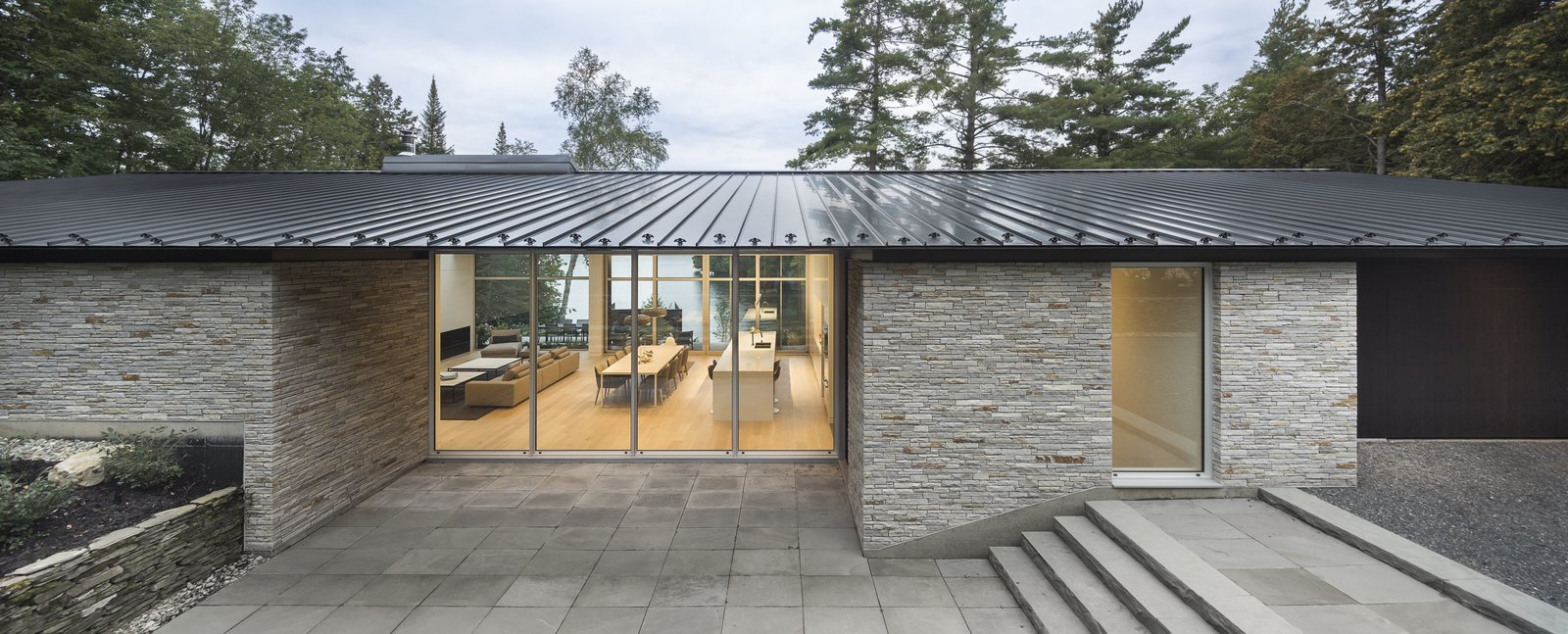 Outdoor, Stone Patio, Porch, Deck, Decomposed Granite Patio, Porch, Deck, Trees, Large Patio, Porch, Deck, and Stone Fences, Wall Massive volumes of dry stacked, locally supplied granite supports the roof.  Best Photos from A Lakeside Retreat in Quebec Looks Sharp With a Blade-Like Roof