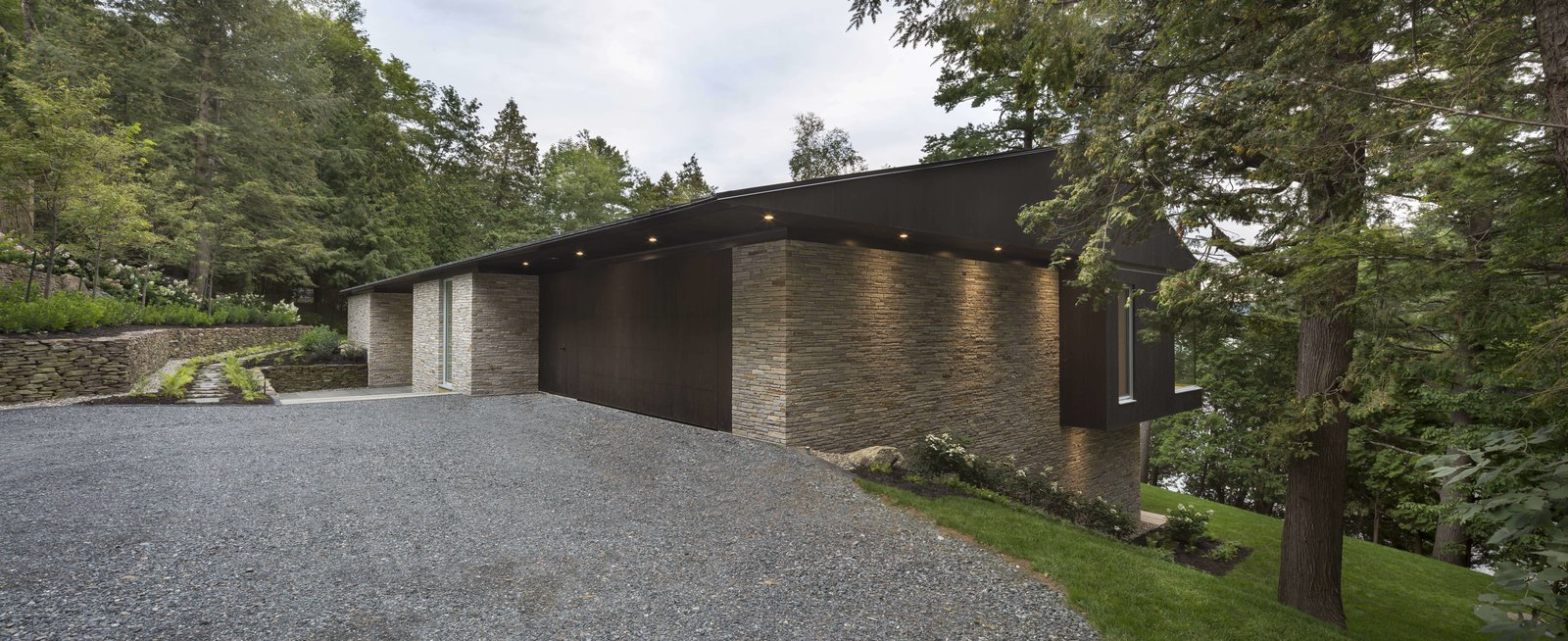 Exterior, Metal, Stone, Shed, and House A home designed by Quebec-headquartered studio MU Architecture.  Best Exterior Metal Stone Photos from A Lakeside Retreat in Quebec Looks Sharp With a Blade-Like Roof
