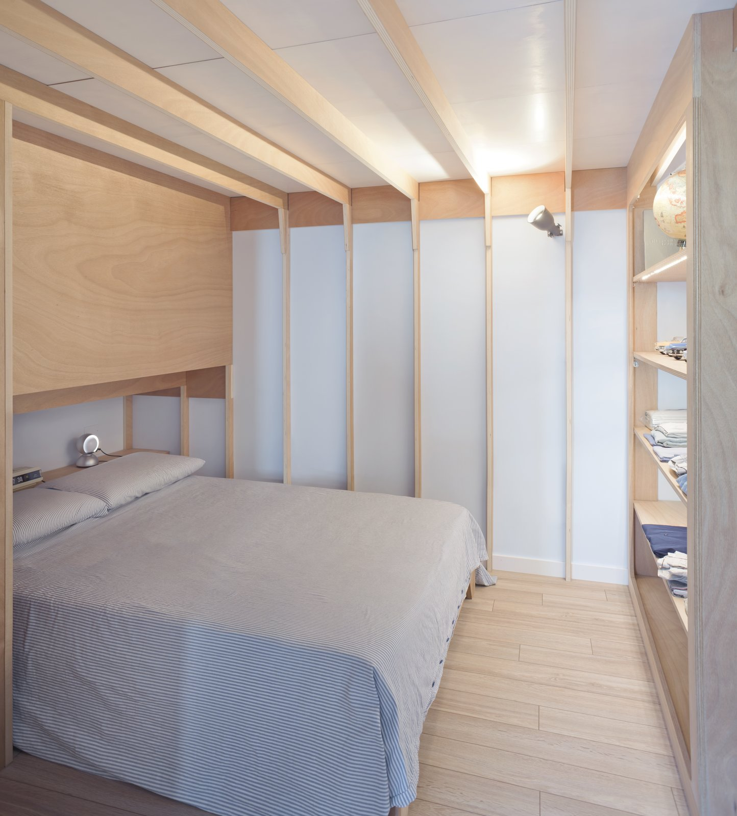 Bedroom, Bed, Wall, Light Hardwood, Shelves, and Table The master bedroom has ribbed ceilings and walls that recall nautical frames.  Best Bedroom Wall Light Hardwood Shelves Photos from A Tiny Apartment in the Italian Riviera Takes Cues From Nautical Design