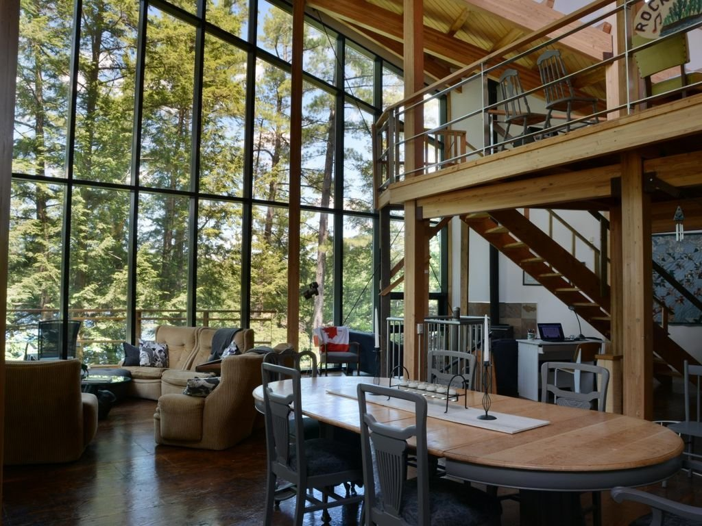 Living Room, Table, Dark Hardwood Floor, and Chair A home with tall glass walls near Lake Rosseau in Ontario, Canada.  Photo 8 of 8 in 8 Glass Houses You Can Rent Right Now
