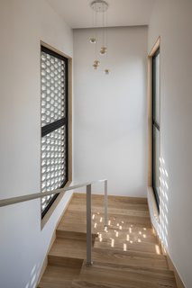A staircase with white walls and light colored wood floors.