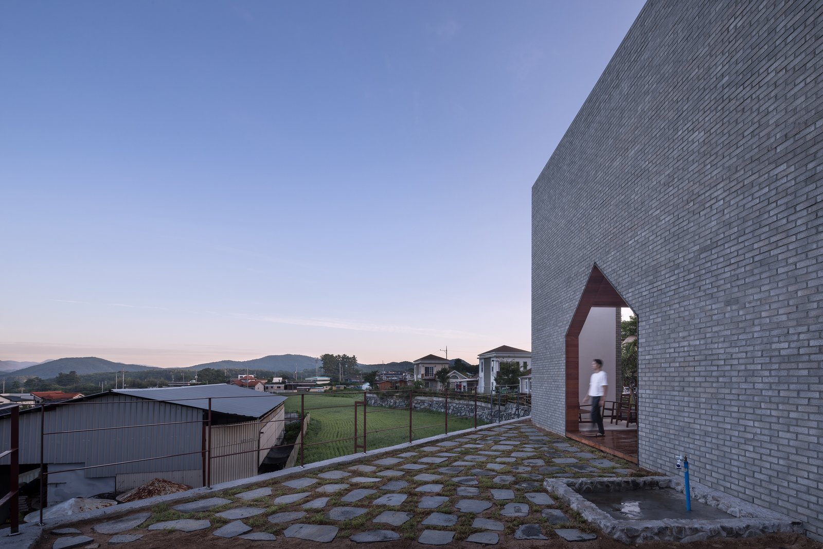 Outdoor, Back Yard, Metal, Large, and Stone A raised terrace at the back of the house.  Outdoor Metal Stone Back Yard Photos from A Gabled Corridor Runs Through This Playful South Korean Home