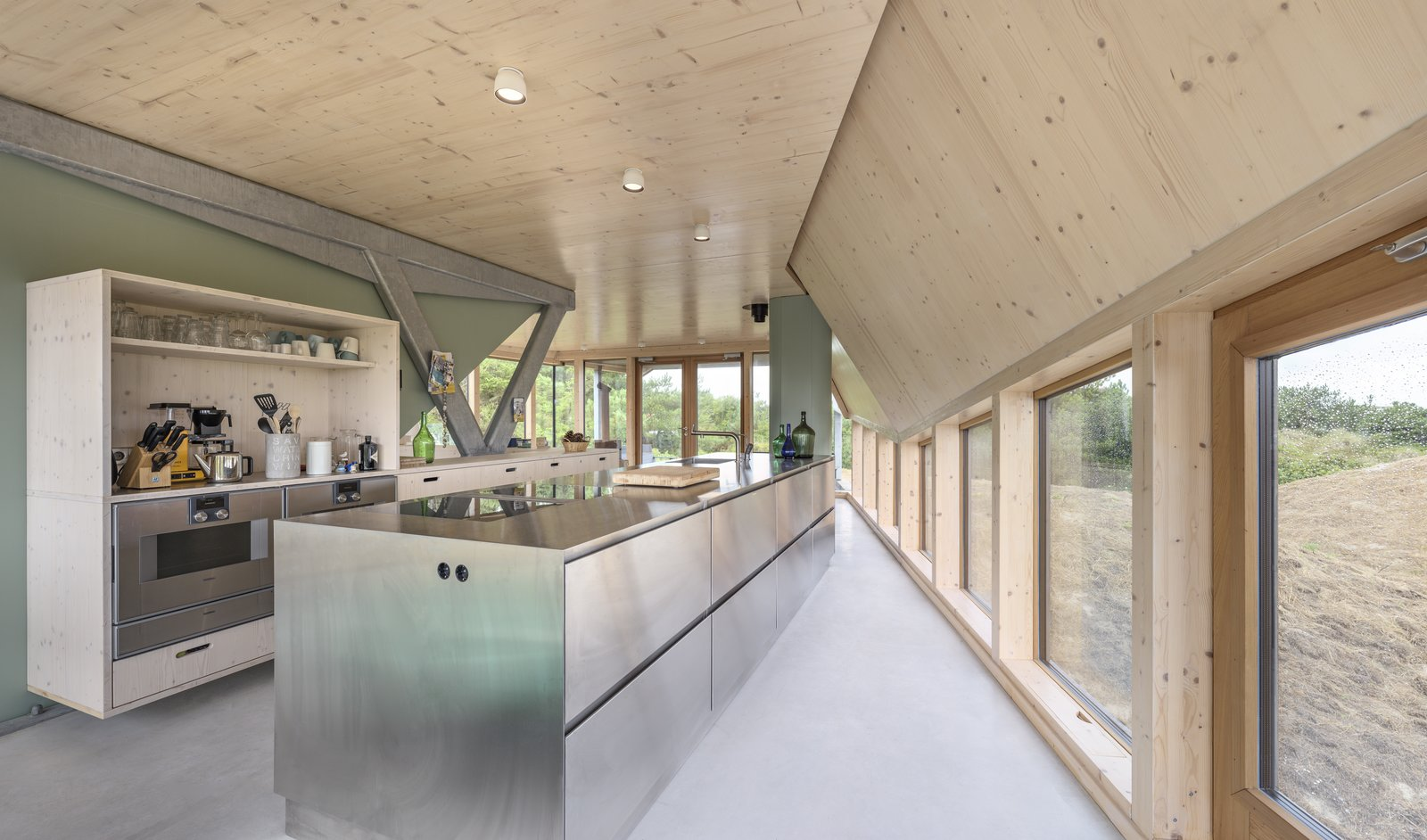 Kitchen, Wood, Ceiling, Metal, Wall Oven, Drop In, Wood, Wood, Open, and Cooktops The open plan kitchen on the ground floor.  Dwell's Favorite Kitchen Metal Wall Oven Wood Photos from A Tent-Shaped Home in the Netherlands Crouches Between Natural Dunes