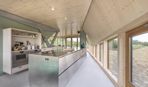 The open plan kitchen on the ground floor. Tagged: Kitchen, Wood, Ceiling, Metal, Wall Oven, Drop In, Wood, Wood, Open, and Cooktops.  Best Kitchen Wood Cooktops Photos from A Tent-Shaped Home in the Netherlands Crouches Between Natural Dunes