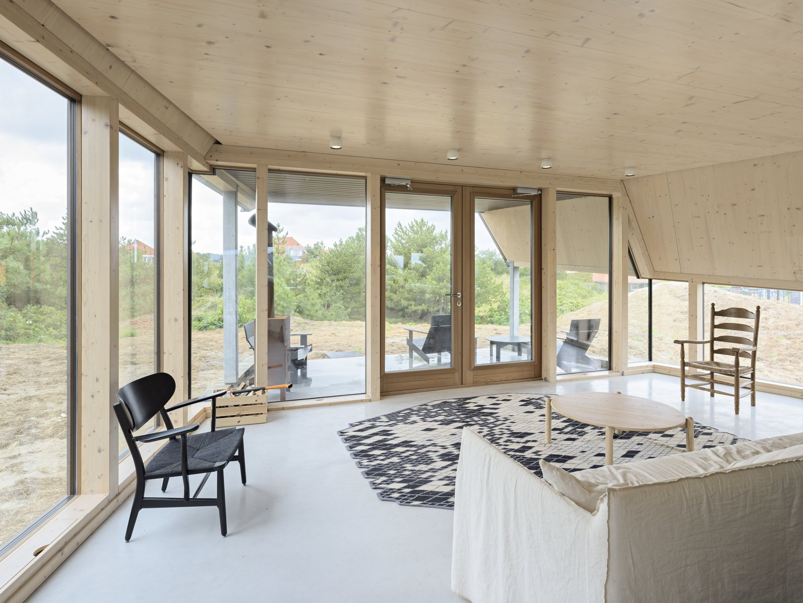 Living Room, Sofa, Ceiling Lighting, Chair, Rug Floor, and Coffee Tables The porch is easily accessible from the living lounge.  Photo 8 of 11 in A Tent-Shaped Home in the Netherlands Crouches Between Natural Dunes