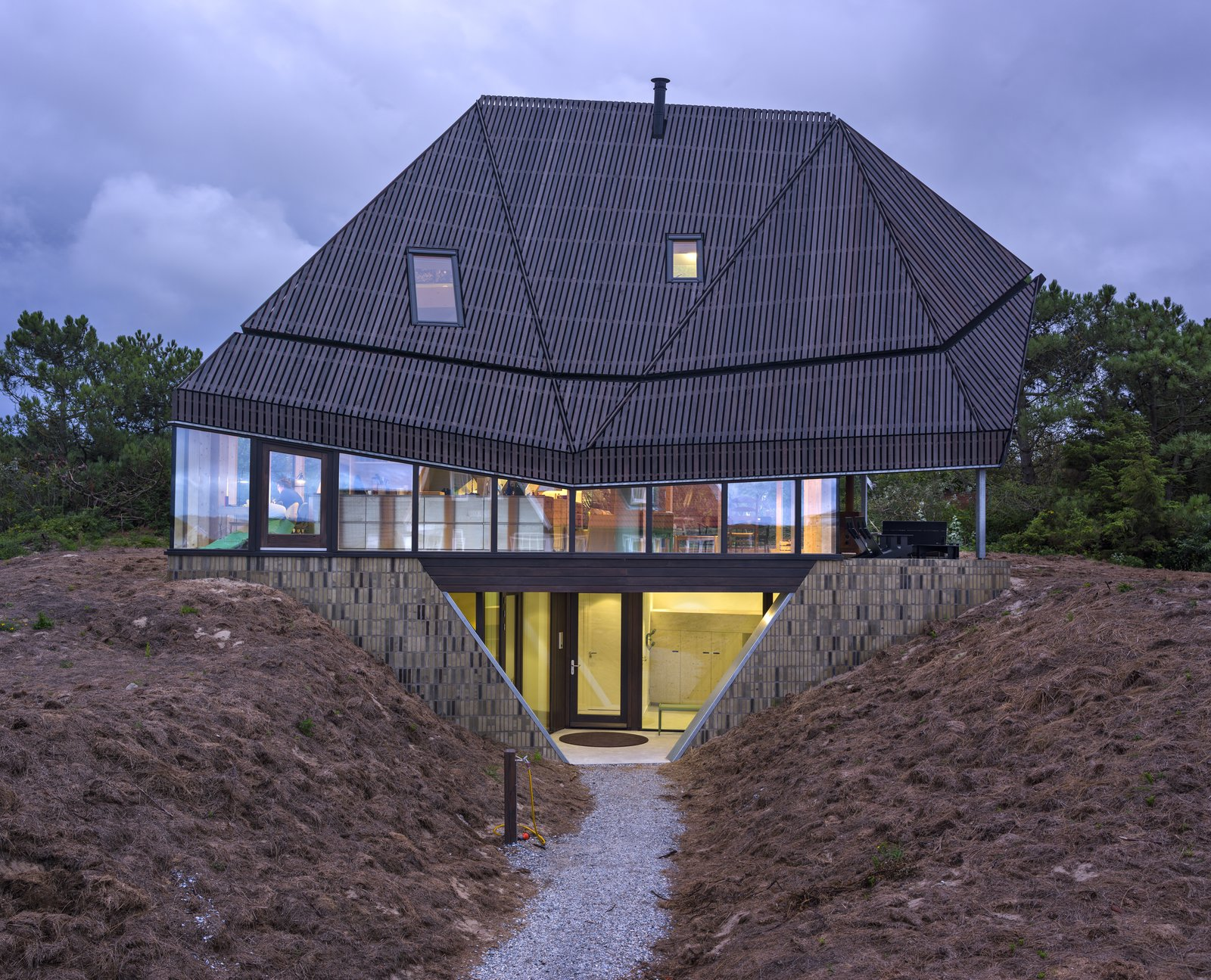 Exterior, House Building Type, and Glass Siding Material A concrete basement  – where the bedrooms are located – is sunk beneath the dunes.  Photo 1 of 11 in A Tent-Shaped Home in the Netherlands Crouches Between Natural Dunes