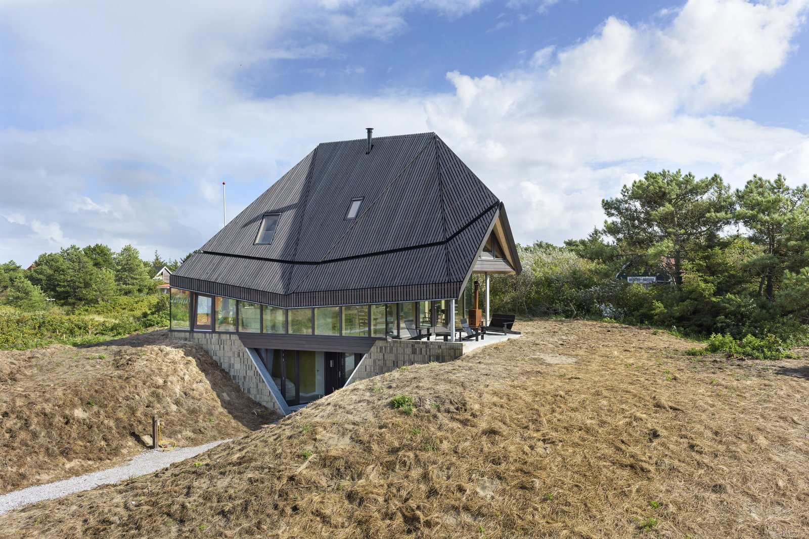 Exterior, House Building Type, and Glass Siding Material Located on the top of a sand dune, the Vlieland house is dominated by a high roof that was inspired by the De Waard Albatross tent, a popular pyramidal camping tent designed by Dutch tent makers De Waard in 1961. The ground floor—where the communal areas like the living lounge, kitchen, and covered terrace are located—are fitted on all sides with glass to maximize views.  Photos from 50 Jaw-Dropping Glass Houses That Shatter Expectations