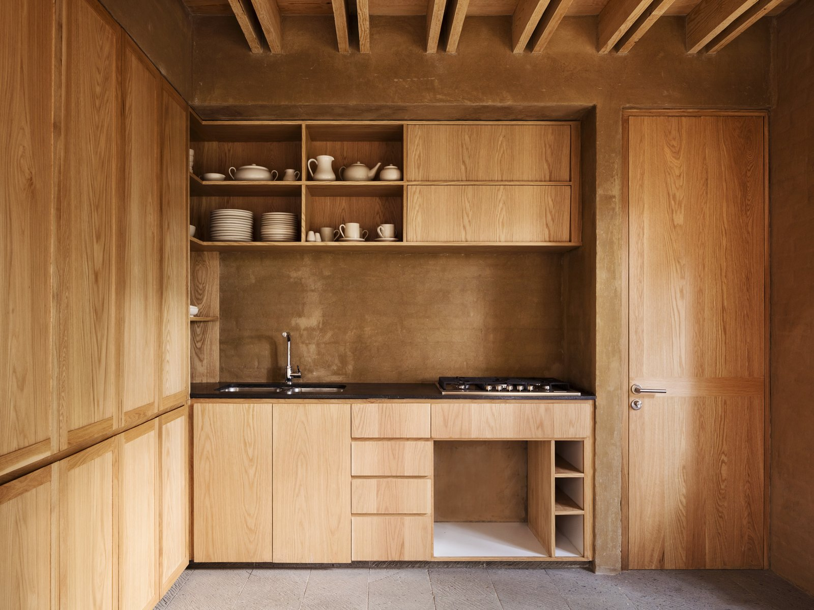 Kitchen, Wood Cabinet, Brick Backsplashe, Range, Undermount Sink, and Open Cabinet A simple wood-finished kitchen.  Photos from Five Cubist Hideaways Peek Out From a Mexican Pine Forest