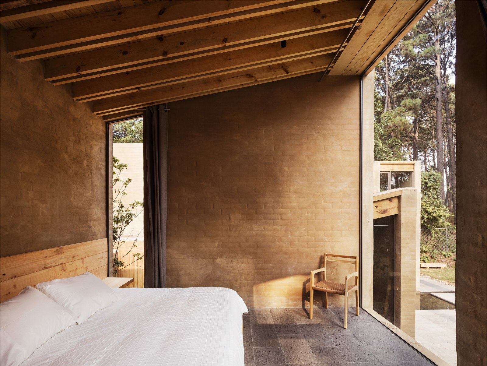 Bedroom, Bed, and Chair A sun-drenched bedroom on the ground level.  Photos from Five Cubist Hideaways Peek Out From a Mexican Pine Forest