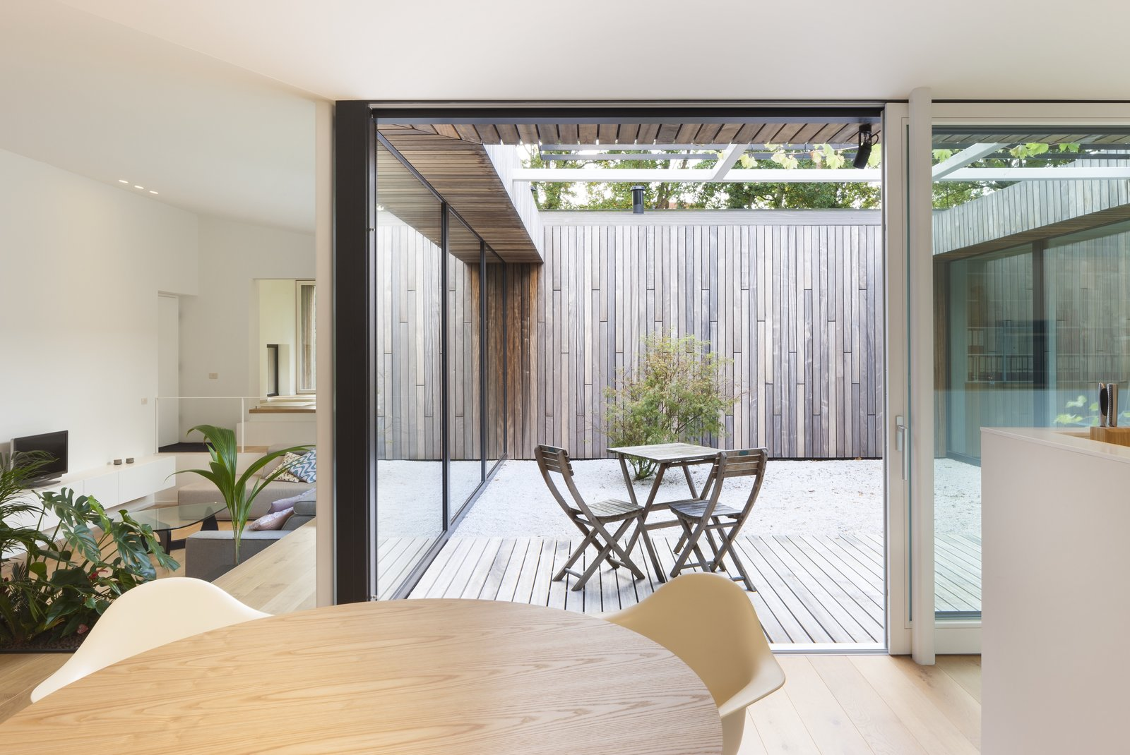Outdoor, Shrubs, Wood Patio, Porch, Deck, Wood Fences, Wall, Vertical Fences, Wall, Small Patio, Porch, Deck, and Hardscapes The courtyard allows light to penetrate deep into the room.  Best Photos from A Belgian Architect's Courtyard House Offers Work/Life Balance