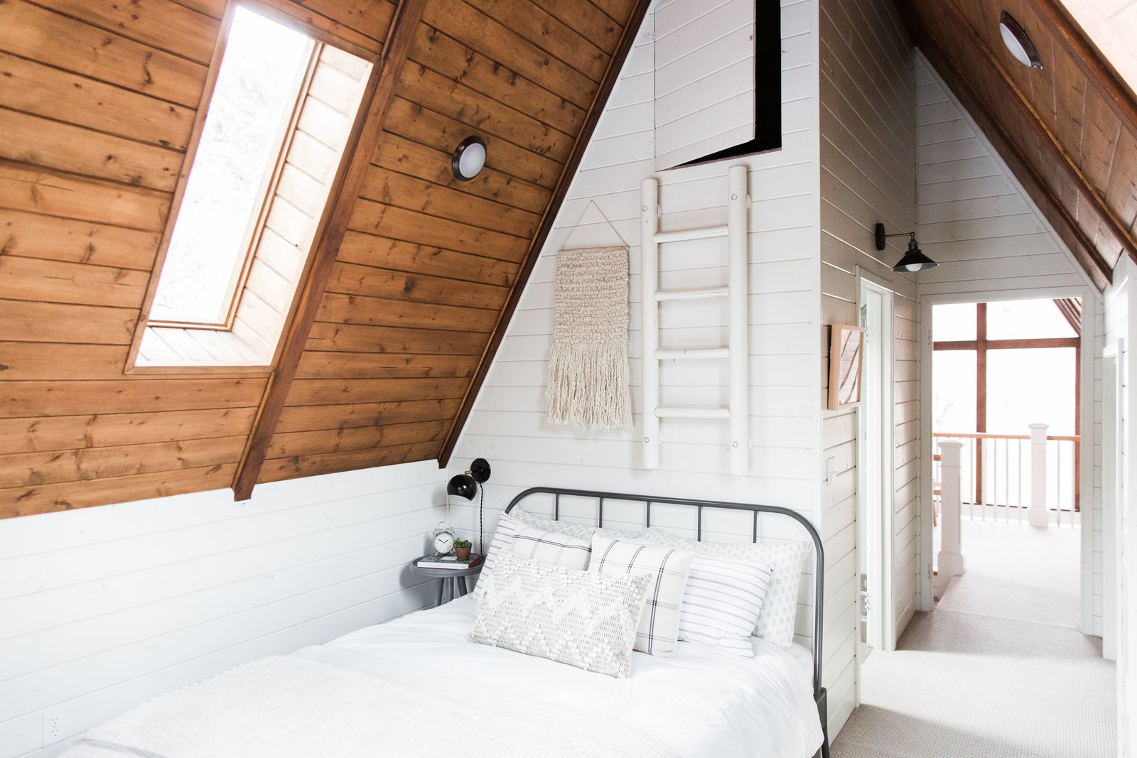 Bedroom, Bed, Table Lighting, and Night Stands Plaid pillows and a weave on the wall bring folk-art feel to the bedroom.  Photo 7 of 14 in Before & After: An A-Frame Cabin Boasts Serious Scandinavian Vibes