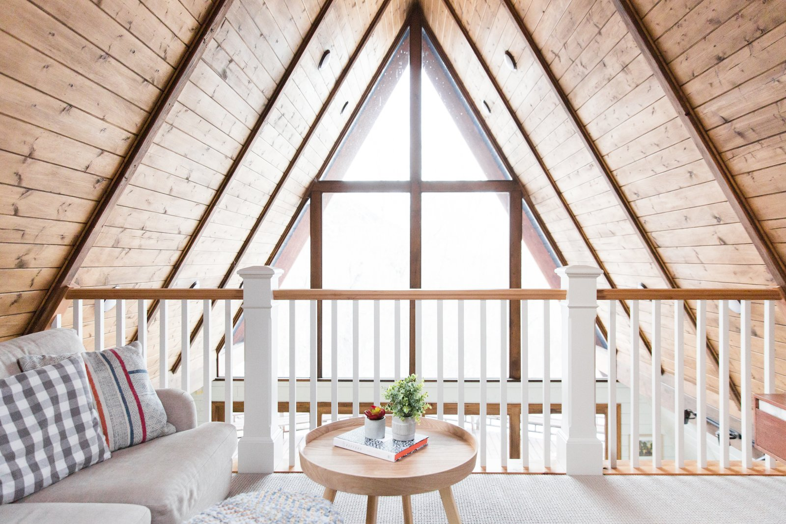 Living Room, Coffee Tables, Carpet Floor, and Sofa Light streams through the full-glass frontage to brighten the lofted lounge area.  Photo 13 of 14 in Before & After: An A-Frame Cabin Boasts Serious Scandinavian Vibes