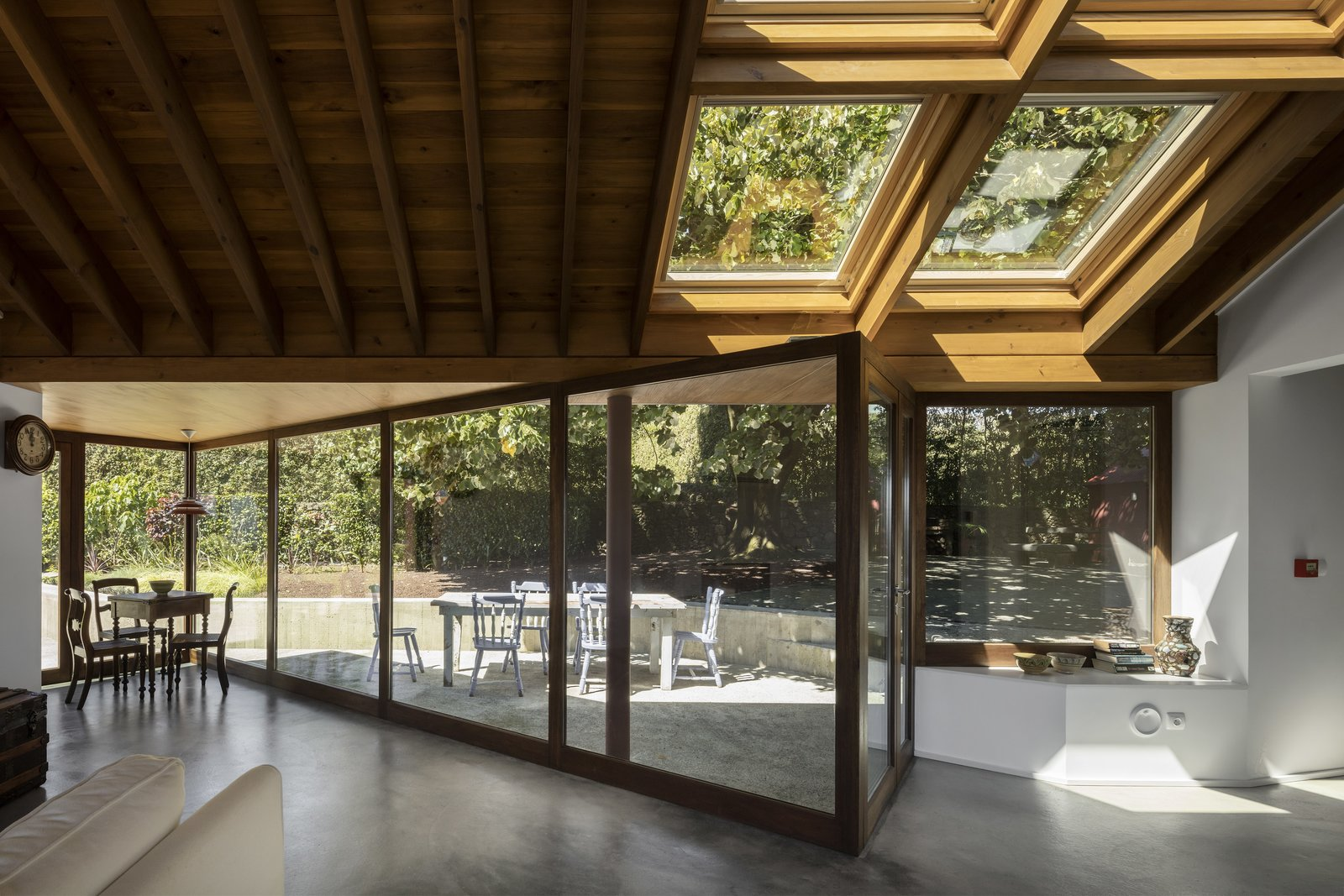 Windows, Skylight Window Type, Sliding Window Type, and Wood Fully-glazed walls and skylights flood the living space with sunlight.  Photo 11 of 14 in A Bright Red Island Residence Embraces a Linden Tree