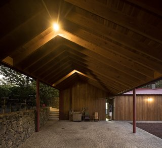 A wide, open-air, stone-paved corridor with a saltbox roof shelter