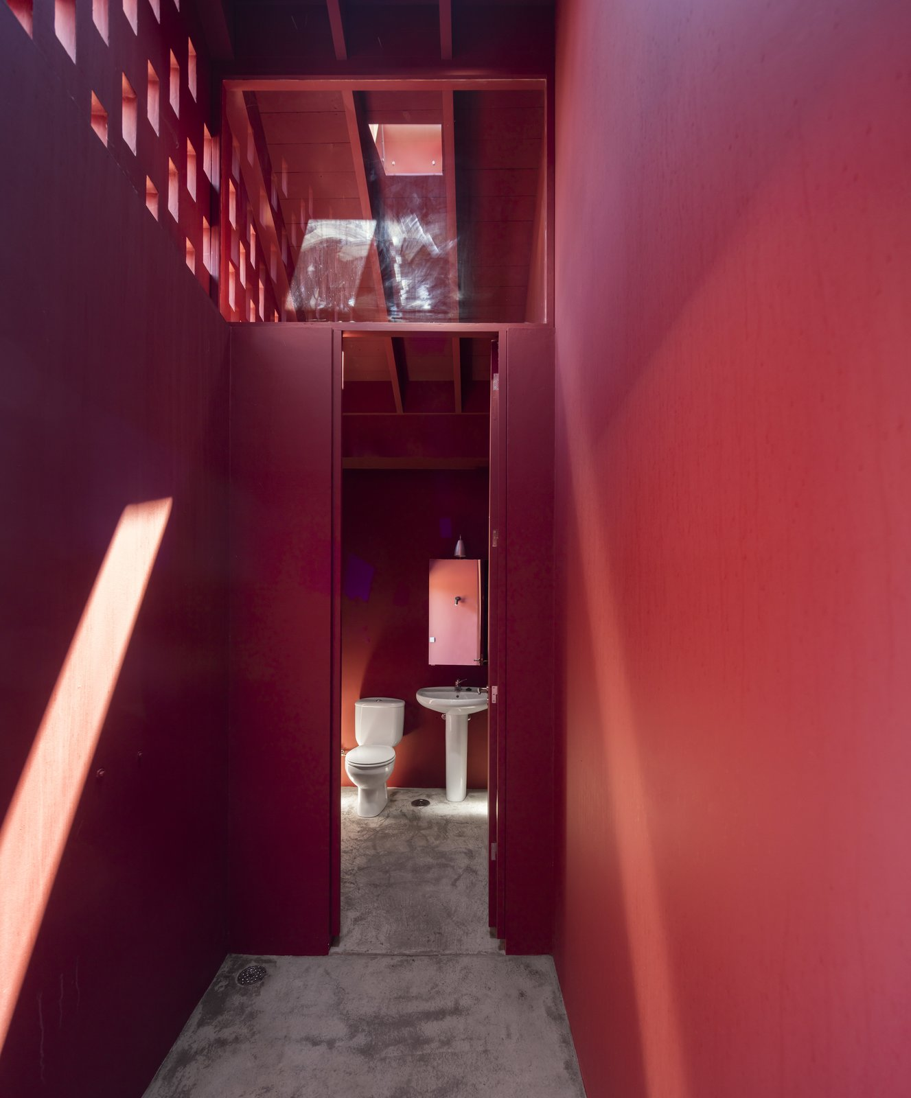 Bath Room, Two Piece Toilet, and Pedestal Sink A bathroom with red walls and ceilings.  Photo 13 of 14 in A Bright Red Island Residence Embraces a Linden Tree
