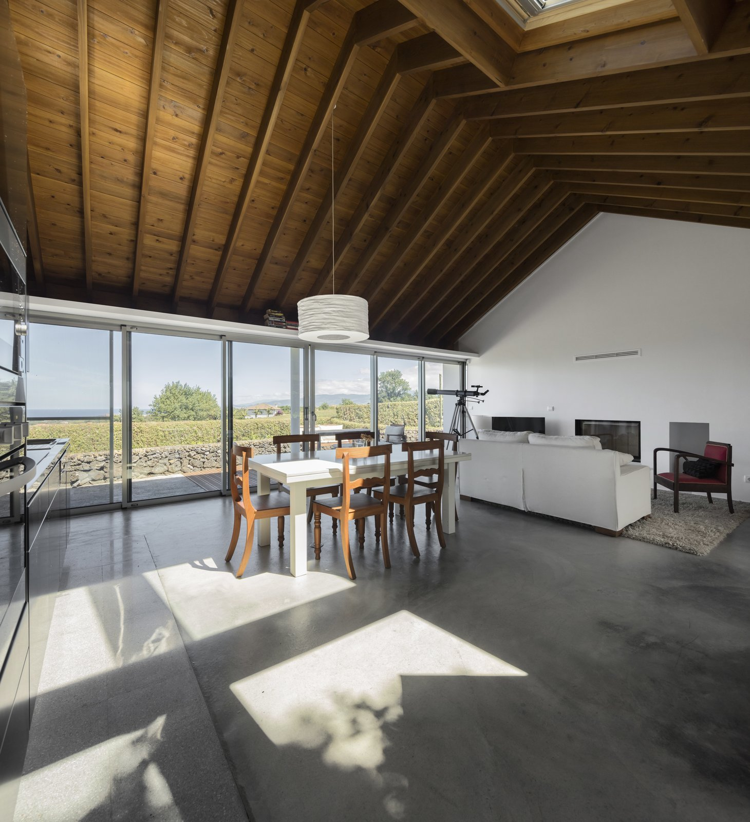 Dining Room, Chair, Pendant Lighting, Concrete Floor, and Table The western windows of the living room look out to coast.  Photo 8 of 14 in A Bright Red Island Residence Embraces a Linden Tree