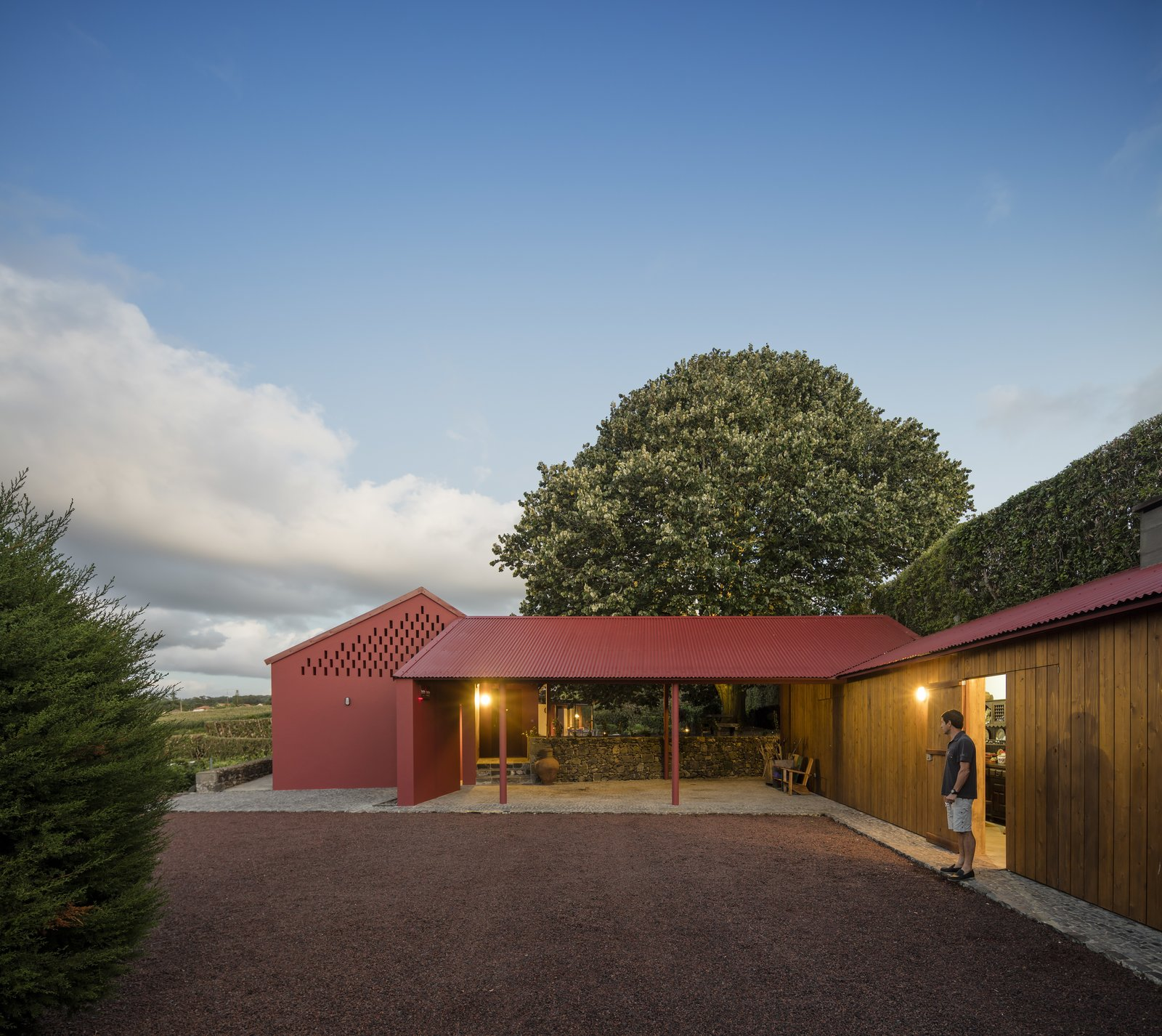Exterior, House Building Type, Shed RoofLine, Wood Siding Material, and Metal Roof Material A wide, open-air, stone-paved corridor connects two volumes.  Photo 2 of 14 in A Bright Red Island Residence Embraces a Linden Tree