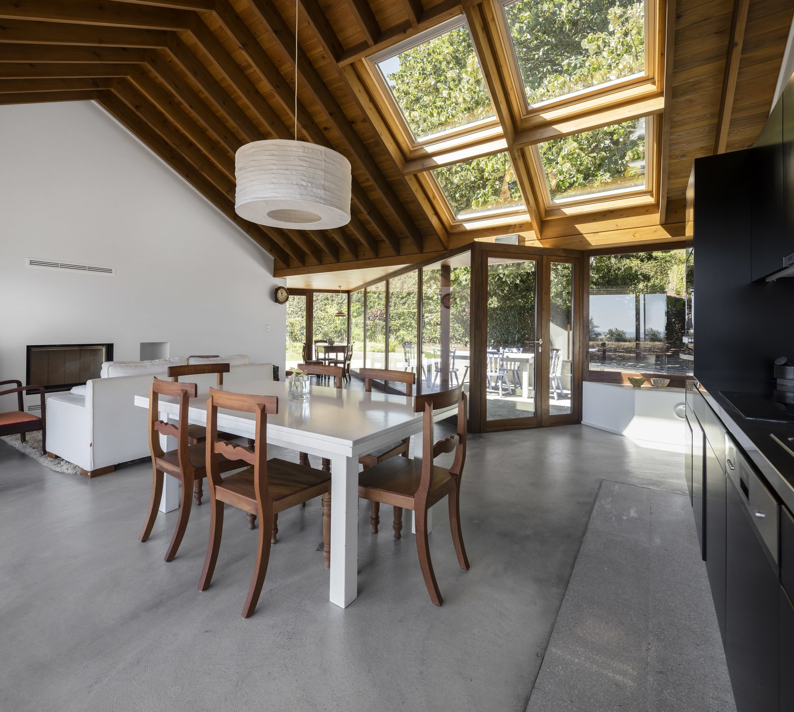 Dining Room, Concrete Floor, Chair, and Table A simple, open plan living, dining and kitchen area that almost feels like part of the courtyard outdoors.  Photo 9 of 14 in A Bright Red Island Residence Embraces a Linden Tree