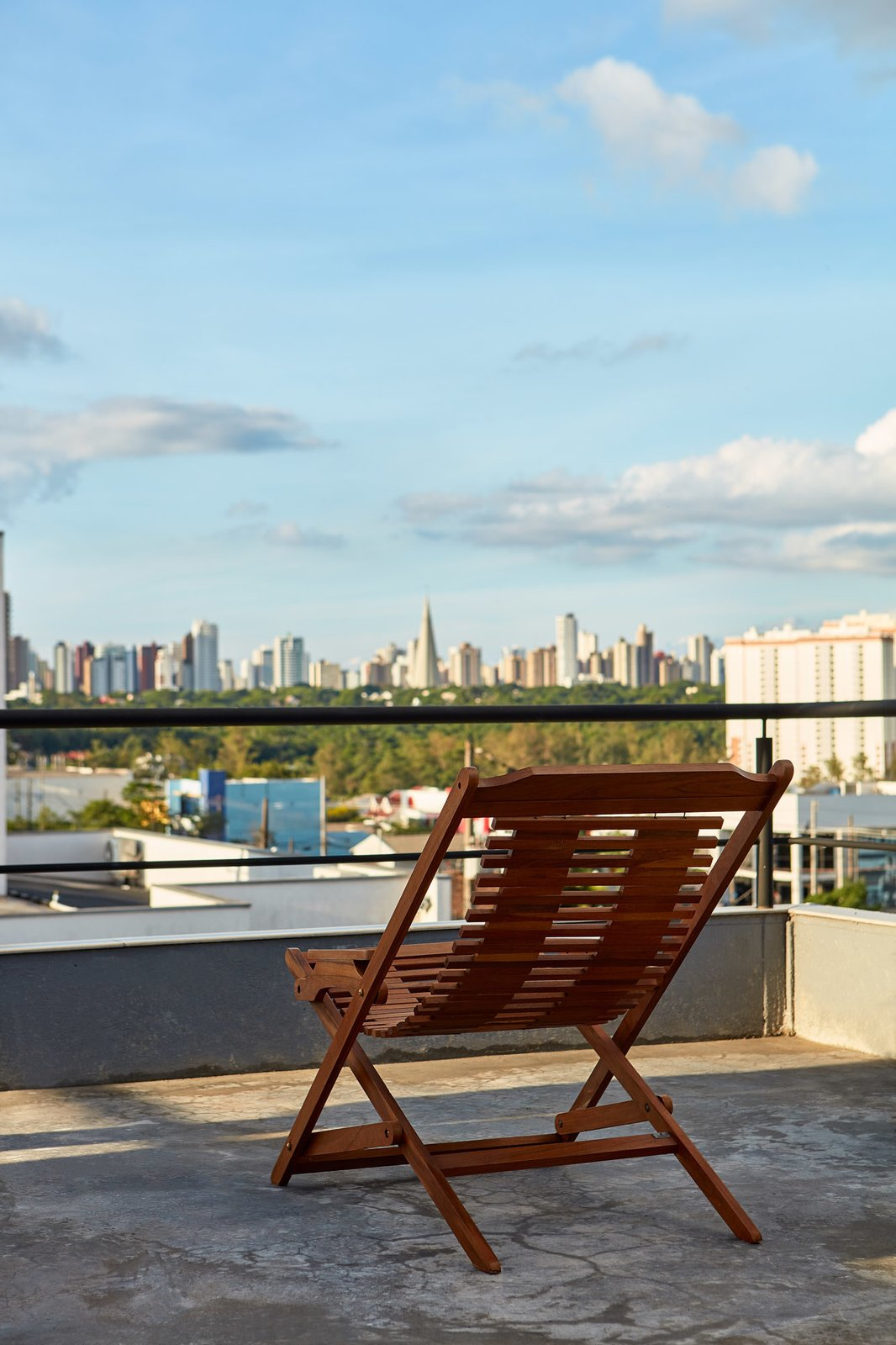 Outdoor, Rooftop, and Concrete Patio, Porch, Deck The house sits at an elevated position, offering great views of the city.  Photo 13 of 14 in This Slender Concrete Home in Brazil Feels Like an Urban Jungle
